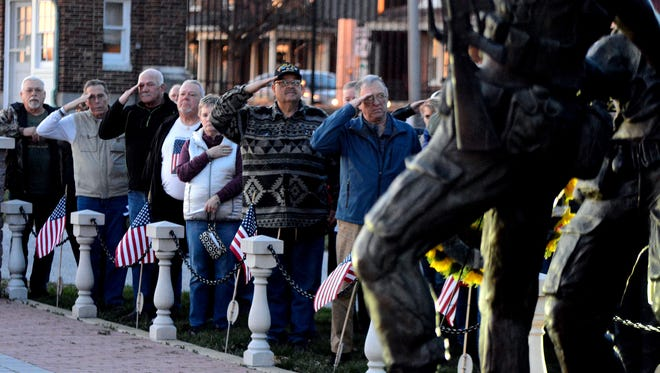 Veterans salute while Taps is played during a candlelight service at the York Vietnam War Memorial on the 1st Annual National Vietnam War Veterans Day, Wednesday, March 29, 2017. The John A. Pavoncello photo