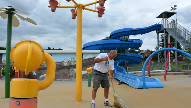 Russ Jacobs sweeps the splash pad as he prepares for the season opener Saturday at Green Valley Swimming Pool & Sports Club, 1725 Poplars Rd in West Manchester Township, Wednesday, May 24, 2017. The membership swim club features three pools, batting cages, basketball courts and more. John A. Pavoncello photo
