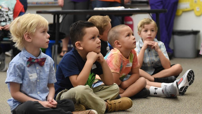 Kindergarteners sit listening to a story being read in their classroom on his first day of Kindergarten at Jesse Hall Elementary on Monday August 14, 2017.