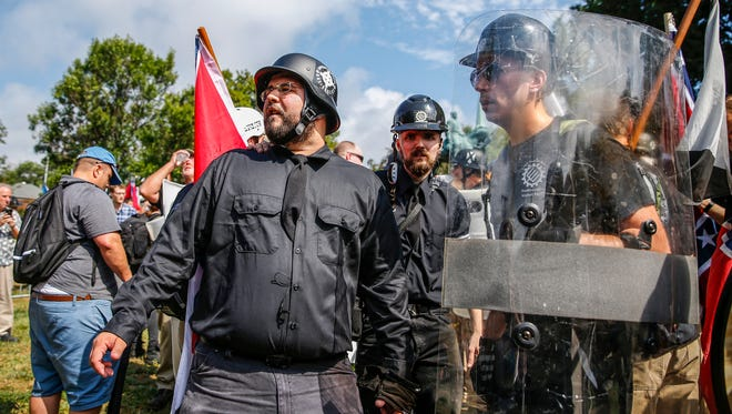 With a guard always attached to his back, Matt Heimbach, right, a white nationalist who calls Indiana home, eyes the crowd that has assembled to counterprotest at Emancipation Park during the 'Unite the Right' rally in Charlottesville, Va., on Saturday, August 12, 2017.