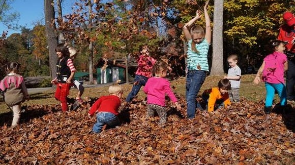 Kids play games in fall leaves at a past Lake Julian