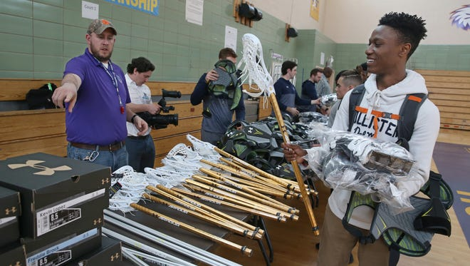 Rochester Knighthawks Executive VP of Business Operations Nate Snyder, left, points out the new boxes of cleats as East High's Marquis Reed admires his brand new stick at East High School Tuesday, April 11, 2017.  The Knighthawks donated Under Armour gear to the high school lacrosse team as part of their ongoing program of starting boys and girls varsity lacrosse in the city next school year.