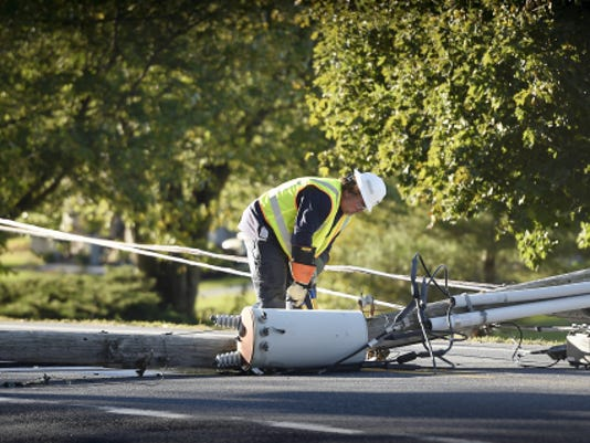 "A Met-Ed ""trouble worker"" works at clearing power lines from West Main Street, Bethel Township, after a car crashed into a utility pole. The driver was trapped in the car until the power lines were de-energized."