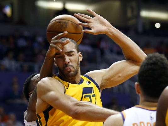 Utah Jazz center Rudy Gobert, middle, gets fouled by Phoenix Suns guard Troy Daniels, rear, during the first half of an NBA basketball gam  Friday, Feb. 2, 2018, in Phoenix. (AP Photo/Ross D. Franklin)