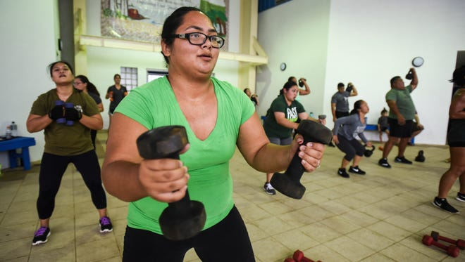 Bridal Boot Camp recruit Holi Tainatongo powers through some strength training during a workout session with fitness trainer Ray Chargualaf at the Paseo on Friday, Feb. 3, 2017.