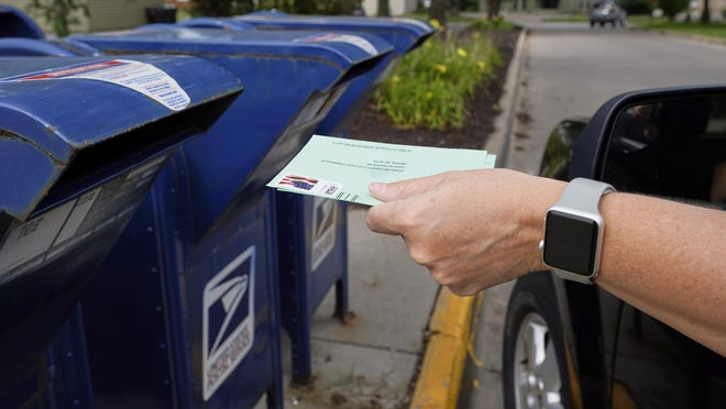 In this Tuesday, Aug. 18, 2020, file photo, a person drops applications for mail-in-ballots into a mailbox in Omaha, Neb. Data obtained by The Associated Press shows Postal Service districts across the nation are missing the agency's own standards for on-time delivery as millions of Americans prepare to vote by mail.