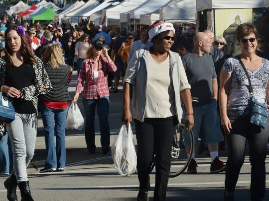 People enjoy the Ventura Winter Wine Walk & Holiday Street Fair in downtown Ventura last year.