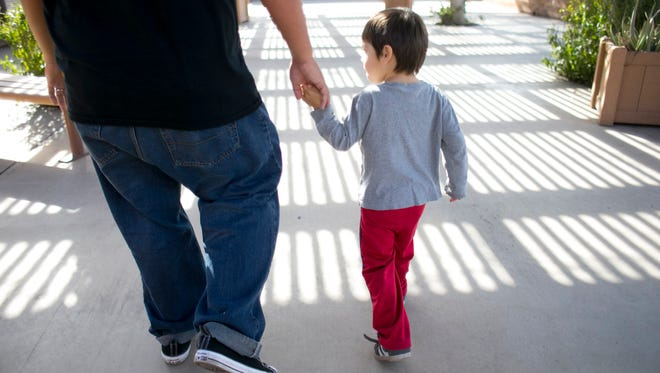 A child development specialist walks with a 3-year-old boy at Child Crisis Arizona in Phoenix on Jan. 28, 2016.