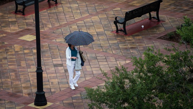 Judi Walker, of Port St. Lucie, a part-time recreation aide at the Port St. Lucie Civic Center, tries to stay dry as she leaves work Monday, July 31, 2017, as rain passes through the area.