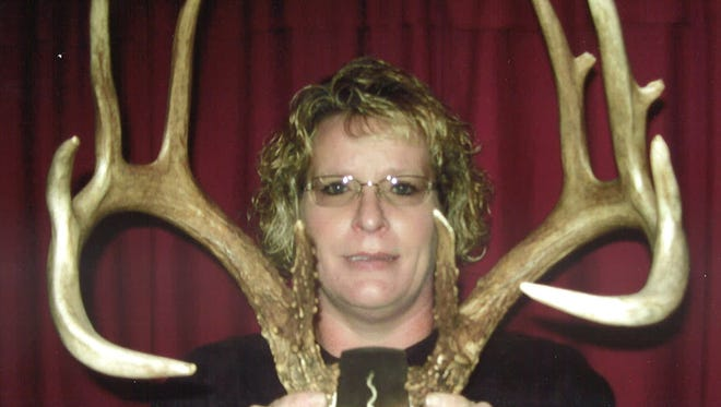 Karla Kloss of Merrill displays the antlers from a 14-point buck she found on opening day of the 2014 gun season.