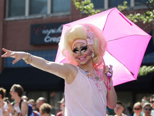 A drag queen known as Trixie Mantel waves at parade-goers