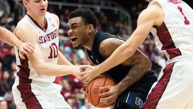 Huskies guard Carlos Johnson (center) isn't afraid to go up against taller players inside, as he shows last week at Stanford.