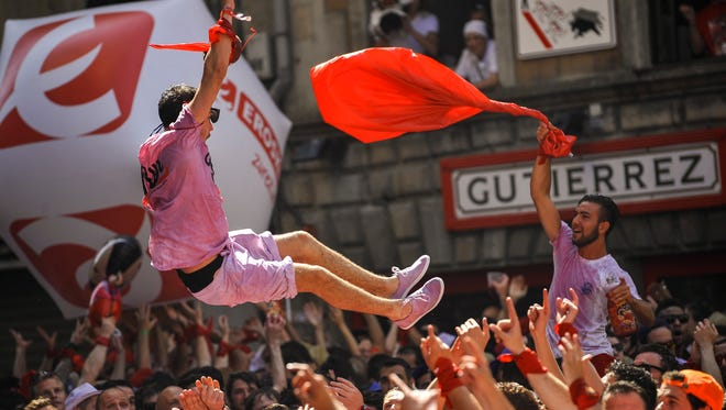 Revelers celebrate during the launch of the 'Chupinazo' rocket, to celebrate the official opening of the 2015 San Fermin Fiestas, in Pamplona, Spain, on July 6, 2015.