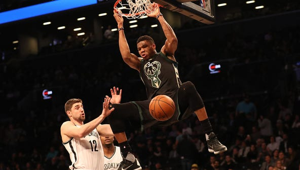 Bucks forward Giannis Antetokounmpo  dunks over Nets