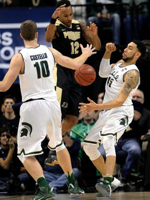 Michigan State senior forward Matt Costello (10) and Michigan State senior guard Denzel Valentine (45) fight for a loose ball after Purdue sophomore forward Vince Edwards (12) looses control of it during the Big Ten Tournament Championship game, Sunday, March, 13, 2016 at Bankers Life Fieldhouse in Indianapolis.
