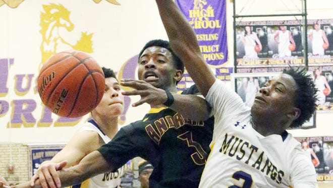 Shahodd Singleton, 3, of Andress runs into heavy traffic from Deion Bauman, 1, left, and Tristen Newton, 2, right of Burges Friday night at Burges. Singleton was fouled on the play.