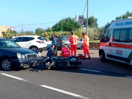 Ambulance personnel tend to a man lying on the ground, later identified as actor George Clooney, after being involved in a scooter accident near Olbia, on the Sardinia island, Italy, Tuesday, July 10.