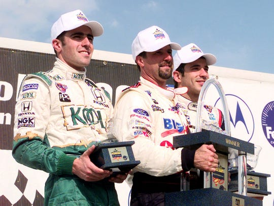 FILE – Michael Andretti (center) winner of the 1999 Motorola 300 held at Gateway International Speedway in Madison Ill. is flanked by Dario Franchitti left third place finisher and Helio Castroneves who finished second in the winner's circle May 29 1999.