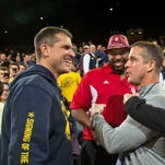 Michigan football coach Jim Harbaugh, left, shares a laugh at a basketball game at the Crisler Center in Ann Arbor on Feb. 2, 2016.
