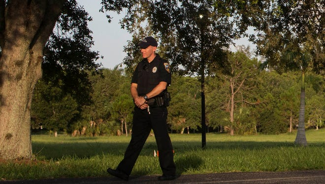 Police guard the perimeter of the Naples Commons, where two bodies were found in the late afternoon of July 7 in Naples. Police received a call from a witness who heard gunshots in the area.