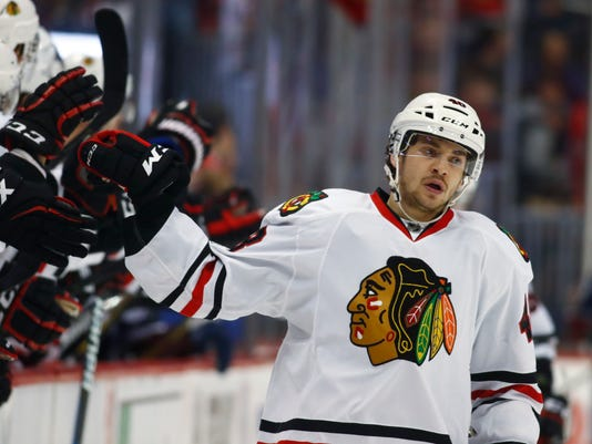 Chicago Blackhawks left wing Vinnie Hinostroza is congratulated as he passes the team box after scoring a goal against the Colorado Avalanche during the third period of an NHL hockey game Tuesday, Jan. 17, 2017, in Denver. The Blackhawks won 6-4. (AP Photo/David Zalubowski)