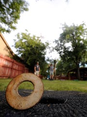 Jacob Thomsen's washer lands on its edge, just missing the hole as it slides across the carpeted board July 27, 2017. On the last Thursday of each month, Meguel Suell holds the Washer Mania tournament in his back yard.