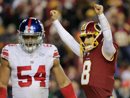 Washington Redskins quarterback Kirk Cousins (8) celebrates wide receiver Josh Doctson's touchdown as he walk past New York Giants defensive end Olivier Vernon (54) during the second half of an NFL football game in Landover, Md., Thursday, Nov. 23, 2017. (AP Photo/Mark Tenally)