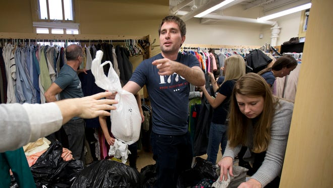 Patrick McAnaney, center, and Morgan Gress, right, from the company 1776, as they volunteer in the clothing room at Bread for the City with a group of their coworkers in Washington on Dec. 16, 2014. Tired of hearing people grouse about a tuned-out, apathetic younger generation? Well, here's a comeback: Today's young Americans are serious when it comes to volunteering.