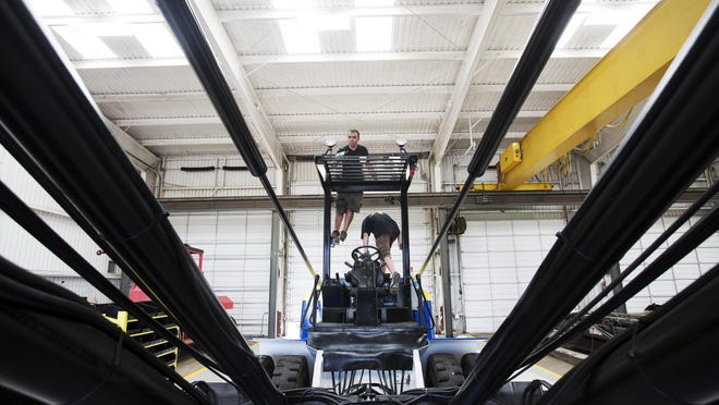 Pawel Socha, left, and Danny Byers, both employees of Hoist Liftruck based out of Chicago, work on a marina forklift at a new location off Alico Road in south Lee County. Hoistlift of Florida, a heavy equipment dealer, held its grand opening Friday. The business is expected to add 50 jobs in the next two years.