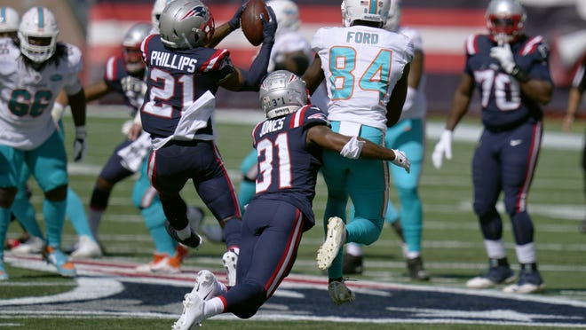 New England Patriots defensive back Adrian Phillips (21) intercepts a pass against the Miami Dolphins in the first half of Sunday's game in Foxboro