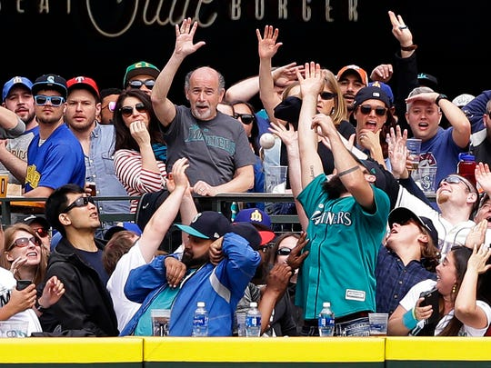 Fans along the outfield rail try to catch a three-run