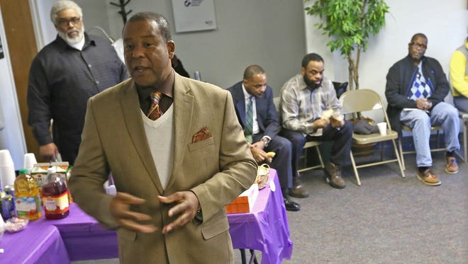 "The Rev. Ty Johnson, a pastor and founder of Churches Take a Corner, speaks at an event in Wilmington about violence and vandalism in the northeast part of the city. ""We speak to the trauma that our kids and our children are experiencing from gun violence in this neighborhood,"" he said."
