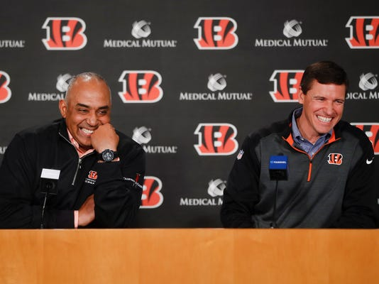 Cincinnati Bengals NFL football head coach Marvin Lewis, left, laughs alongside offensive coordinator Bill Lazor, right, during a news conference following an announcement that they will remain in their positions for an additional two seasons, Wednesday, Jan. 3, 2018, in Cincinnati. (AP Photo/John Minchillo)
