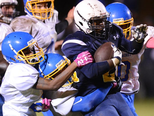 Northampton defenders attempt to bring down Chincoteague's VoShawn Davis (22) as he carries the ball during the Ponies' homecoming football game on Friday, Oct. 14, 2016. Chincoteague won the game 49-45.