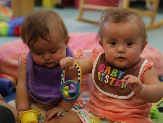 Nine-month-old Simone Laender looks up as she plays with her twin sister Scarlett at the tribe's daycare center on the Menominee Indian Reservation in Keshena, Thursday, August 7, 2014. The center operates at just over half of capacity because of a lack of funding to hire additional staff.