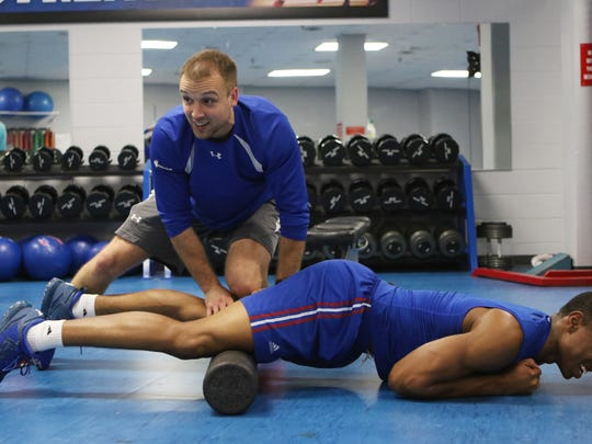 Louisiana Tech strength coach Casey Cathrall uses a foam roller to help forward Oliver Powell stretch after a weight lifting session on Wednesday, Nov. 9, 2016.