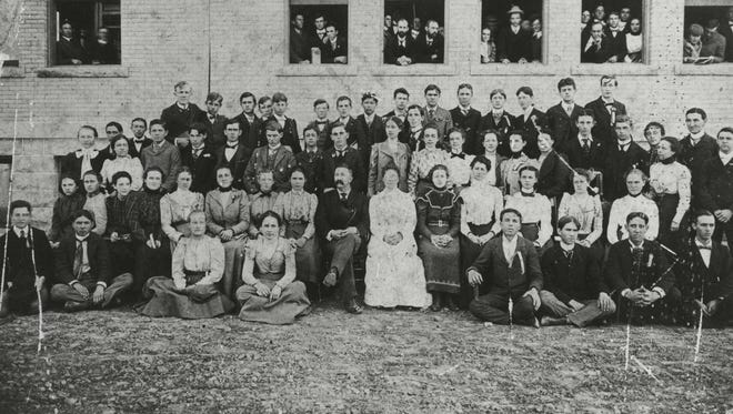 The first students to attend Eastern Indiana Normal University pose in a photo believed to have been taken in 1899 when Administration Building was new (note the lack of grass). President and Mrs. F. A. Z. Kumler and probably their daughter are seated in the center for the first row.