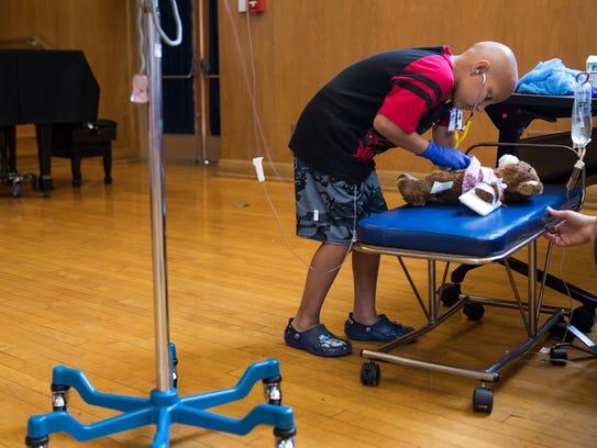 Eight-year-old Austin Sanchez checks the hart beat