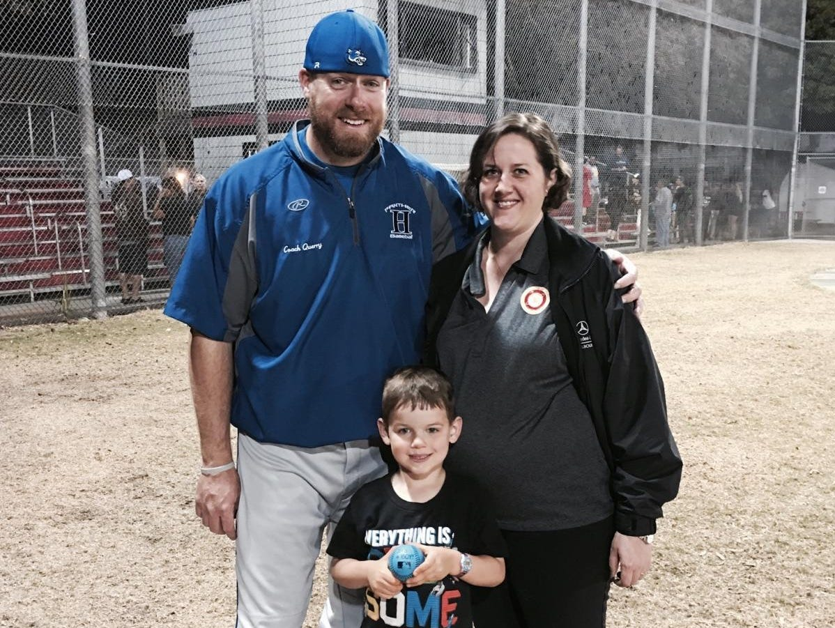 Heritage baseball coach Rob Querry poses with wife Julia and son Brady after she used a blue baseball to tell him he'd be having a son.
