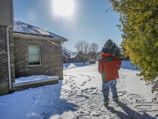 Joey Myles, a homeowner in Franklin Township's Franklin Trace neighborhood, was in a monthslong back-and-forth with his HOA over getting solar panels. Here Myles clears the snow from the solar panels he ended up having to install on the north side of his home on Wednesday, Jan. 17, 2018.