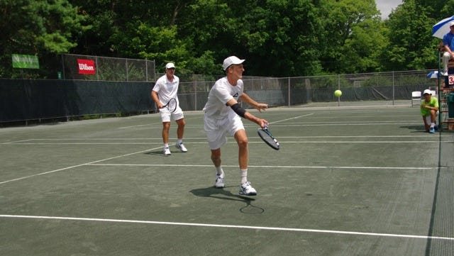 Tanner Smith (with father Peter Smith in the background) lunges for a volley during the championship match of the National Father & Son Clay Court Tournament, which was held Sunday at the Cincinnati Tennis Club.
