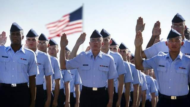 Airmen lift their right hand as they repeat the oath of enlistment at the Air Force Basic Training graduation ceremony, Lackland Air Force Base, Texas.