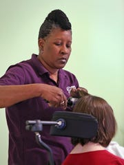 Kathy Young, 54, an employee with Home Instead Senior Care, is shown drying her client's hair on March 18, 2015. Black women in Indiana earn 67 cents for every dollar a white male makes, and for Hispanic women it's even less at 54.4 cents, according to the National Women's Law Center. Overall, women make 74 cents for every dollar a white man earns.