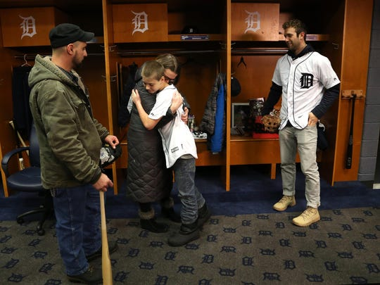 Caleb Bowman, left, looks on as his wife, Miranda, and son, Hunter, hug during a moment inside the Tigers locker room as his new friend, Tigers pitcher Daniel Norris, watches and smiles as well on Feb. 13.