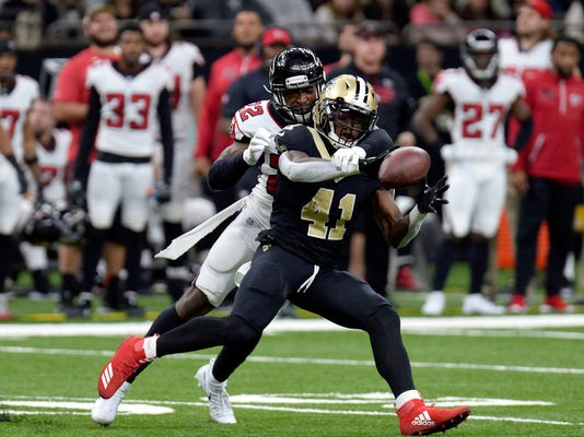 FILE - In this Dec. 24, 2017, file photo, Atlanta Falcons strong safety Keanu Neal (22) tries to break up a pass intended for New Orleans Saints running back Alvin Kamara (41) during the first half of an NFL football game in New Orleans. Kamara says the NFL has fined him $6,079 for wearing Christmas-themed red cleats with white trim during last Sunday's victory over Atlanta. Kamara says it was worth it and says he's hoping to parlay publicity from his banned holiday cleats into a fundraiser to help supply athletic footwear to children whose families struggle to afford it. (AP Photo/Bill Feig, File)