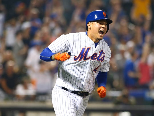 Mets second baseman Wilmer Flores reacts after hitting