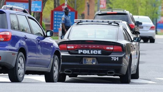 A Delaware State University police vehicle enters the main entrance of the campus.