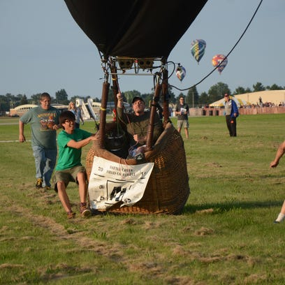 Craig Campbell of Springfield lands his balloon as others also approach the field.