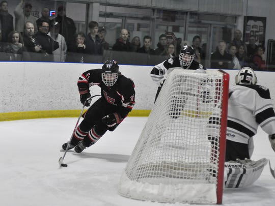 Livonia Churchill's John Doyle (11) circles Plymouth's goal, occupied by netminder Brendan Olepa (1) during Saturday's Division 2 regional final at Arctic Edge.