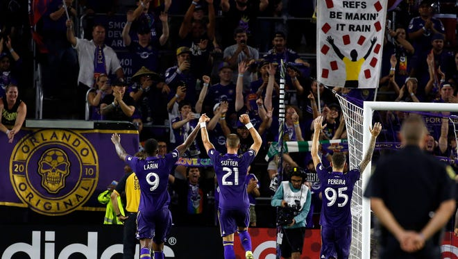 Orlando City SC's Cyle Larin (9), Scott Sutter (21) and Leonardo Pereira (95) celebrate with fans after a draw against the Chicago Fire.